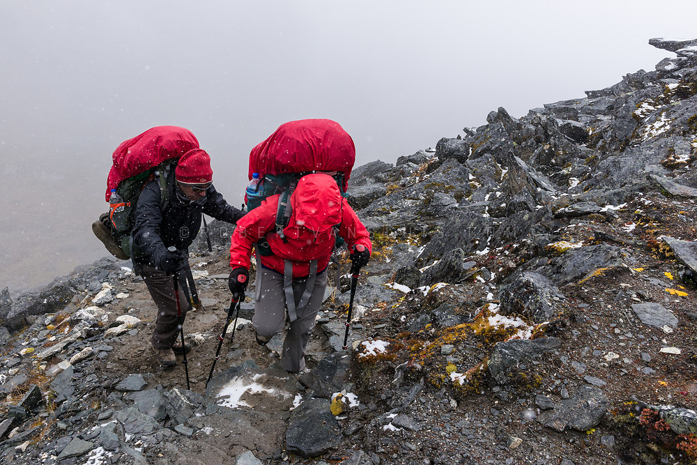 In the Nepal Himalaya, two hikers make their way up towards Kongma La pass in snow. Photo © robertvansluis.com