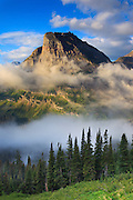 Fog lifts near Heavy Runner Mountain in Glacier National Park, Montana.