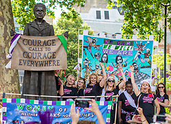 © Licensed to London News Pictures. 10/06/2018. London, UK. A group of women from Essex pose in front of the Millicent Fawcett statue in Parliament Square as thousands of people march through central London wearing green, white and violet, the colours of the Suffragette movement,  to celebrate 100 years votes for women. Photo credit: Rob Pinney/LNP
