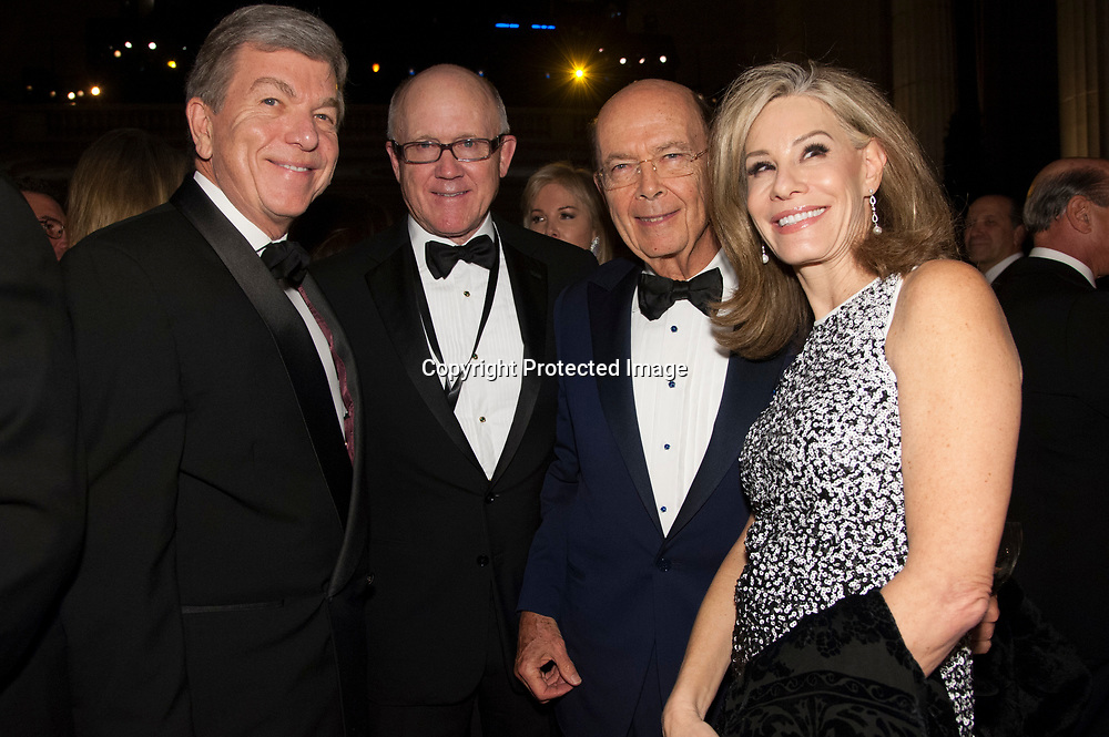 Former Senator Roy Blunt (L), Treasury Secretary nominee Woody Johnson (2nd-L), Wilbert Ross (2nd-rt) and Abigail Perlman Blunt  (R) pose for a photo during the Chairman's Global Dinner at the Andrew W. Mellon Auditorium in Washington DC on January 17, 2017.