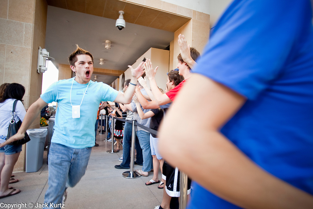 """12 JUNE 2009 -- SCOTTSDALE, AZ: Employees of the new Apple Store in Scottsdale, AZ, run through the line of shoppers sharing """"high fives"""" with them before the store opened Friday. The outlet will be Arizona's largest Apple Store, occupying nearly 10,000 square feet in the Outdoor Lifestyle Center in the Scottsdale Quarter. The store, the fifth in the Phoenix area, uses a radically different design from other Apple Stores in some respects. Ceilings in the building are approximately 20 feet high, and lined with a 75-foot long skylight, reducing dependence on artificial lighting. Aiding the skylight is an all-glass front and rear, permitting visitors to see directly through the store. More than one thousand people lined to get into the store during the grand opening. Photo by Jack Kurtz"""