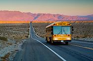 School bus on long straight two lane desert road at sunrise, Anza Borrego Desert State Park, San Diego County, California