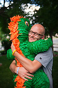 Jake Welch embraces a dinosaur pinata in his front yard in Boulder, Colorado.