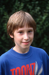 Portrait of young boy standing in garden smiling,