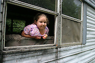 Girl peers from window of dilapidated trailer amid poverty of Appalachia in Magoffin County near Salyersville, Kentucky