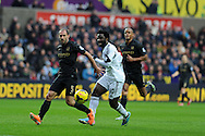 Swansea city's Wilfried Bony (10) is challenged by Man city's Pablo Zabaleta. Barclays Premier league, Swansea city v Manchester City at the Liberty Stadium in Swansea,  South Wales on  New years day Wed 1st Jan 2014 <br /> pic by Andrew Orchard, Andrew Orchard sports photography.