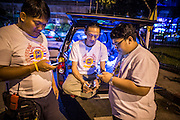 """30 NOVEMBER 2012 - BANGKOK, THAILAND: Medics with the Ruamkatanyu Foundation check their smart phones between calls near the Ekamai BTS stop during a Friday night shift. The Ruamkatanyu Foundation was started more than 60 years ago as a charitable organisation that collected the dead and transported them to the nearest facility. Crews sometimes found that the person they had been called to collect wasn't dead, and they were called upon to provide emergency medical care. That's how the foundation medical and rescue service was started. The foundation has 7,000 volunteers nationwide and along with the larger Poh Teck Tung Foundation, is one of the two largest rescue services in the country. The volunteer crews were once dubbed Bangkok's """"Body Snatchers"""" but they do much more than that now.    PHOTO BY JACK KURTZ"""