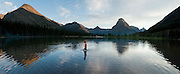 """A boy walks in Pray Lake beneath Sinopah Mountain (8271 feet or 2521 meters) at sunset in Glacier National Park, Montana, USA. Since 1932, Canada and USA have shared Waterton-Glacier International Peace Park, which UNESCO declared a World Heritage Site (1995) containing two Biosphere Reserves (1976). Rocks in the park are primarily sedimentary layers deposited in shallow seas over 1.6 billion to 800 million years ago. During the tectonic formation of the Rocky Mountains 170 million years ago, the Lewis Overthrust displaced these old rocks over newer Cretaceous age rocks. Glaciers carved spectacular U-shaped valleys and pyramidal peaks as recently as the Last Glacial Maximum (the last """"Ice Age"""" 25,000 to 13,000 years ago). Of the 150 glaciers existing in the mid 1800s, only 25 active glaciers remain in the park as of 2010, and all may disappear by 2020, say climate scientists. (Panorama stitched from 4 overlapping images.)"""