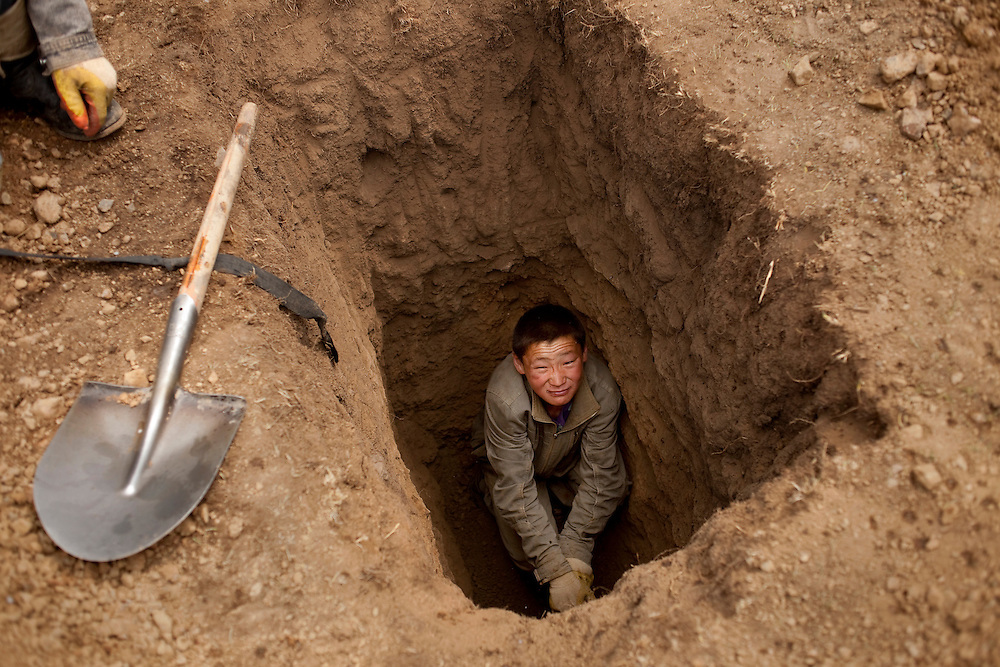 """A young man in a pit mine just large enough for himself. He is looking for the """"gold dirt"""". The sought after dirt is of a different shade that indicates it may contain gold. The dirt is then loaded into sacks or into flatbed trucks and brought to an area with water so it can be panned in order to separate the gold flecks from the dirt."""