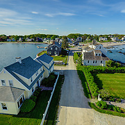A real estate marketing image for a home in Kennebunk, Maine, showing the home's dramatic setting with water views to the front and rear. See the next image for comparison images.