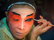 "18 AUGUST 2014 - BANGKOK, THAILAND:   A member of the Lehigh Leng Kaitoung Opera troupe applies her makeup before a performance at Chaomae Thapthim Shrine, a small Chinese shrine in a working class neighborhood of Bangkok. The performance was for Ghost Month. Chinese opera was once very popular in Thailand, where it is called ""Ngiew."" It is usually performed in the Teochew language. Millions of Chinese emigrated to Thailand (then Siam) in the 18th and 19th centuries and brought their culture with them. Recently the popularity of ngiew has faded as people turn to performances of opera on DVD or movies. There are still as many 30 Chinese opera troupes left in Bangkok and its environs. They are especially busy during Chinese New Year and Chinese holiday when they travel from Chinese temple to Chinese temple performing on stages they put up in streets near the temple, sometimes sleeping on hammocks they sling under their stage. Most of the Chinese operas from Bangkok travel to Malaysia for Ghost Month, leaving just a few to perform in Bangkok.     PHOTO BY JACK KURTZ"