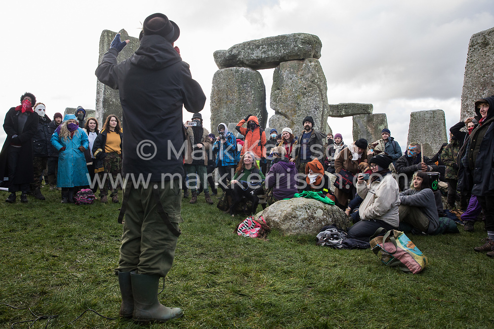 Salisbury, UK. 5th December, 2020. Pete the Temp performs for over one hundred people, including local residents, climate and land justice activists and pagans, during a Mass Trespass at Stonehenge. The trespass was organised in protest against the approval by Transport Secretary Grant Shapps of a £1.7bn project for a two-mile tunnel beneath the World Heritage Site and a further eight miles of dual carriageway for the A303, as well as the government's £27bn Road Investment Strategy 2 (RIS2).