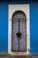 Wrought Iron Doorway in Fontainhas which is the old European or more specifically Portuguese quarter of Panjim.  Fontainhas has a certain mood that is different rom the rest of Panjim.  Its charm has been left intect thanks  to the colorful paint jobs of buildings in the area bright  blue, ochre and various shades of red.