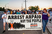 """23 JUNE 2012 - PHOENIX, AZ:  Children carry a banner around the Maricopa County Jail Saturday. About 2,000 members of the Unitarian Universalist Church, in Phoenix for their national convention, picketed the entrances to the Maricopa County Jail and """"Tent City"""" Saturday night. They were opposed to the treatment of prisoners in the jail, many of whom are not convicted and are awaiting trial, and Maricopa County Sheriff Joe Arpaio's stand on illegal immigration. The protesters carried candles and sang hymns.     PHOTO BY JACK KURTZ"""