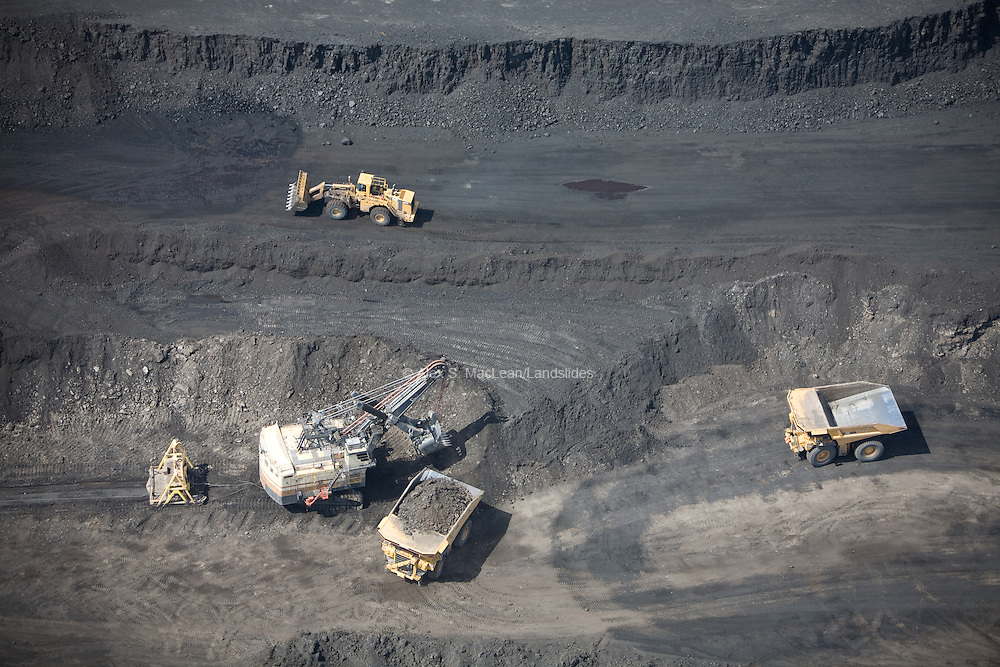 Diesel trucks carrying off rock and extractions of coal by strip mining in the Powder River Basin.