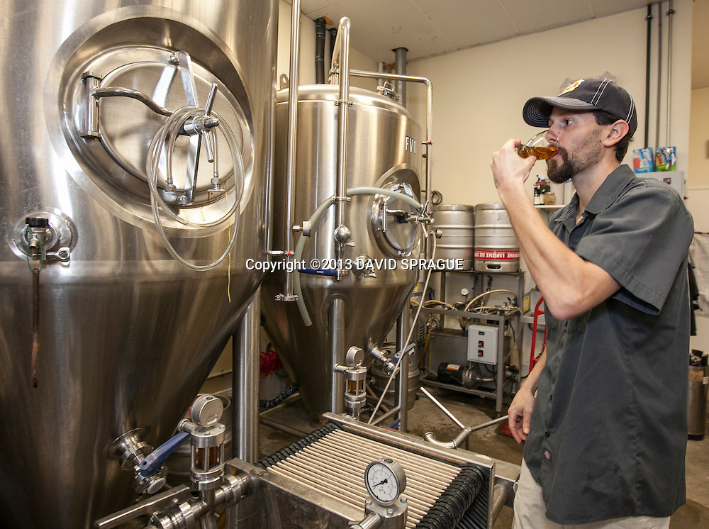Head brewer Dave Griffiths (correct) tastes a beer in the brewery at LadyFace Ale Companie in Agoura Hills, CA. Shot Feb. 5th,  2013 Photo by David Sprague ©2013