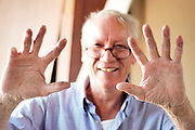 A smiling carpenter in his seventies with nine fingers gives the sign of Ten - excellent