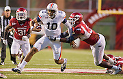 Auburn quarterback Kiehl Frazier (10) gets past Arkansas linebacker Jerry Franklin (34) as safety Jerico Nelson (31) pursues during an NCAA college football game on Saturday, Oct. 8, 2011, in Fayetteville, Ark. (AP Photo/Beth Hall)