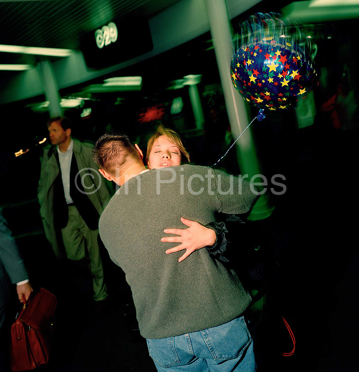 A young man with a Welcome Home balloon, meets his partner after a long absence, in the airport terminal at Chicago-O'Hare airport, Illinois, USA. Waiting for his partner for some hours in the darkened terminal, a late arrival oon this day, the young man has been patient after a slight delay but finally, the girl comes through the arrivals gate to greet her close friend - loving the balloon gesture and pleased to be safely in his arms. Hugging tightly they embrace in front of other passengers before leaving the airport for home, 12 months before the terrorist attacks on America that changed the public's attitude to flying on commercial airliners.
