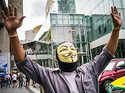"""02 JUNE 2013 - BANGKOK, THAILAND:   A man wearing a Guy Fawkes mask leads anti-government protesters through Bangkok skywalk system. The so called White Mask protesters are strong supporters of the Thai monarchy. About 300 people wearing the Guy Fawkes mask popularized by the movie """"V for Vendetta"""" and Anonymous, the hackers' group, marched through central Bangkok Sunday demanding the resignation of Prime Minister Yingluck Shinawatra. They claim that Yingluck is acting as a puppet for her brother, former Prime Minister Thaksin Shinawatra, who was deposed by a military coup in 2006 and now lives in exile in Dubai.   PHOTO BY JACK KURTZ"""