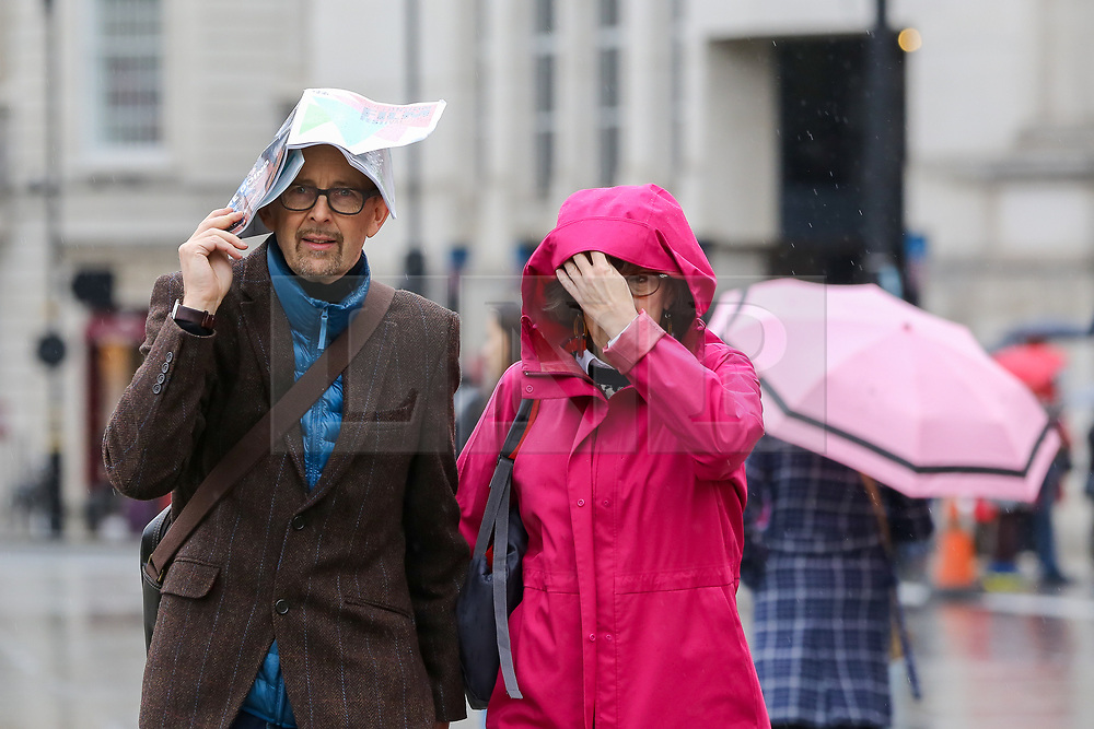 © Licensed to London News Pictures. 07/10/2019. London, UK. A man covers his head from rain with a book on a wet and windy afternoon in Trafalgar Square. Photo credit: Dinendra Haria/LNP