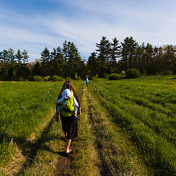 A woman carries her baby through a field in Durham, New Hampshire.