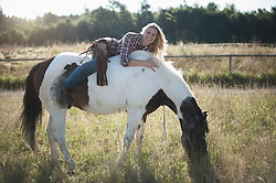 Portrait of a mid adult woman lying on back of horse in farm and smiling, Bavaria, Germany