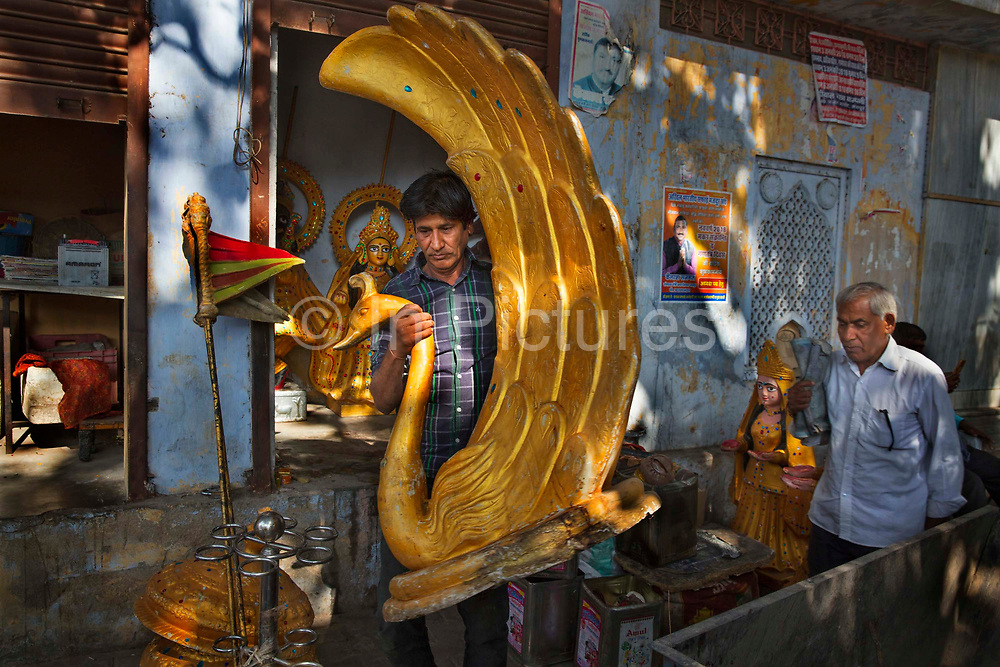 Carpenter carving and painting Hindu shrine objects  on 6th February 2018 in Jaipur, Rajasthan, India.
