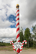 A giant candy stripped pole marking the spot in North Pole, Alaska. North Pole is not actually the geographic northern pole but a Christmas themed town outside Fairbanks.