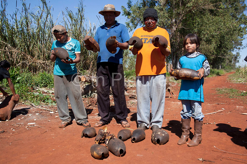 Guarani people showing ant eater shells. The Guarani are one of the most populous indigenous populations in Brazil, but with the least amount of land. They mostly live in the State of Mato Grosso do Sul and Mato Grosso. Their tradtional way of life and ancestral land is increasingly at risk from large scale agribusiness and agriculture. There have been recorded cases and allegations of violence between owners of large farms and the Guarani communities in this region.