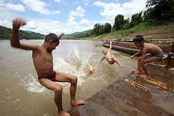 Children play in the river from the location where the old ferry used to cross the river close to the new bridge over the Mekong River to Sayabouri Town.  Sayaboury Province. Lao PDR