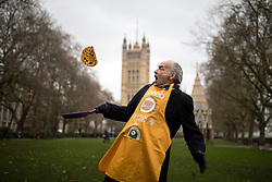 © Licensed to London News Pictures. 13/02/2018. London, UK. Official Race Starter Alastair Stewart OBE flips a pancake of the Rehab Parliamentary Pancake Race 2018 in Victoria Tower Gardens. The Parliament Team - made up of MPs, Lords and Ladies - race in a relay against the Media Team - made up of reporters and presenters - whilst continuously flipping pancakes to celebrate Shrove Tuesday, also known as Pancake Day. Photo credit : Tom Nicholson/LNP