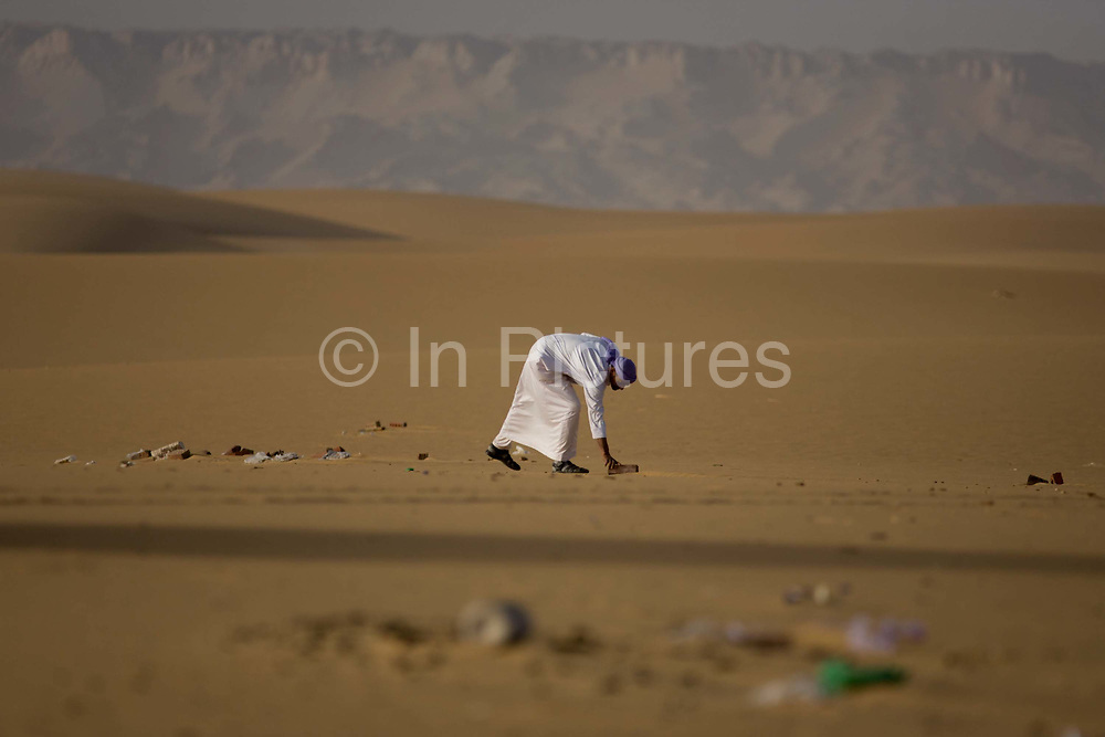 A Bedouin inspects rubbish left in desert sand dunes near the Dahkla Oasis, Western Desert, Egypt. The past few decades have been difficult for traditional Bedouin culture due to changing surroundings and the establishment of new resort towns on the Red Sea coast, such as Sharm el-Sheikh. Bedouins in Egypt are facing a number of challenges: erosion of traditional values, unemployment, and various land issues. The Western Desert covers an area of some 700,000 km2, thereby accounting for around two-thirds of Egypt's total land area. Dakhla Oasis is one of the seven oases of Egypt's Western Desert (part of the Libyan Desert). It lies in the New Valley Governorate, 350 km (220 mi.) and measures approximately 80 km (50 mi) from east to west and 25 km (16 mi) from north to south.