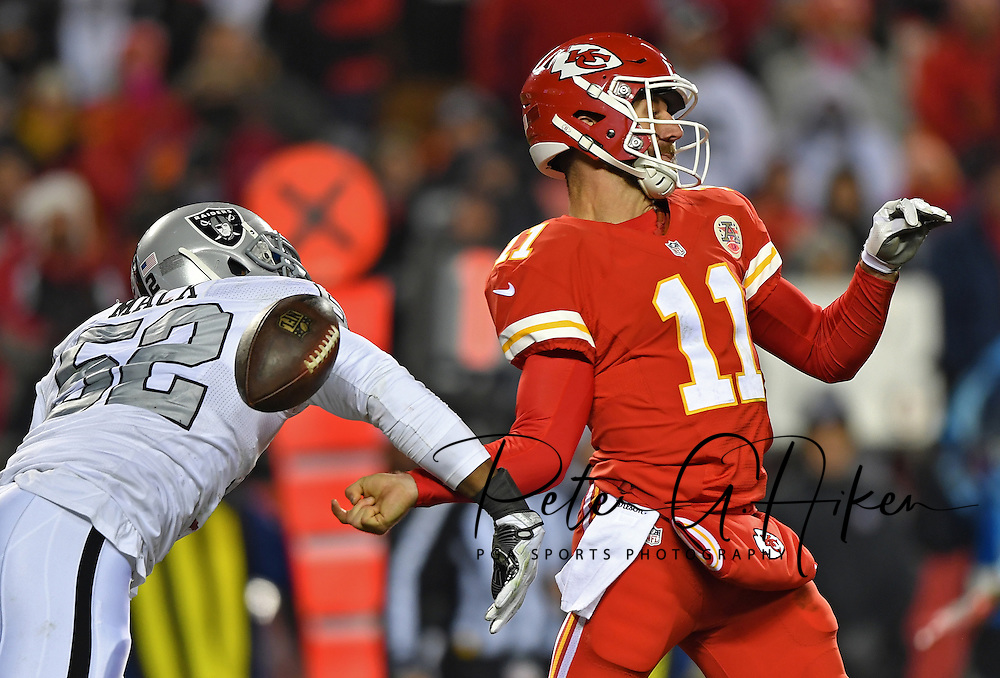 Defensive end Khalil Mack #52 of the Oakland Raiders reaches out to strip the ball from quarterback Alex Smith #11 of the Kansas City Chiefs during the third quarter at Arrowhead Stadium in Kansas City, Missouri.