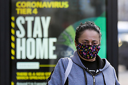 © Licensed to London News Pictures. 30/12/2020. London, UK. A woman wearing a face covering walks in front of the government's 'Coronavirus Tier 4 - Stay Home' publicity poster in north London, as the Medicines and Healthcare Products Regulatory Agency (MHRA) approves the Oxford/AstraZeneca vaccine (codenamed AZD1222 or ChAdOx1) for use in the UK. Health Secretary Matt Hancock has said that the vaccine will be rolled out from 4 January 2021. A number of cities will be put into tougher Tier 4 COVID-19 restrictions after the mutated SARS-Cov-2 virus continues to spread around the country and coronavirus infection rates rise. Photo credit: Dinendra Haria/LNP