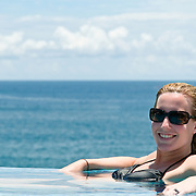 Young woman relaxing in the pool against the ocean.