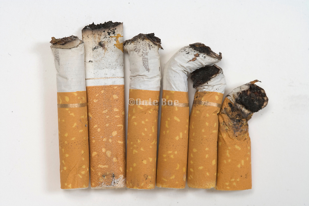 assortment of stubbed out cigarette butts