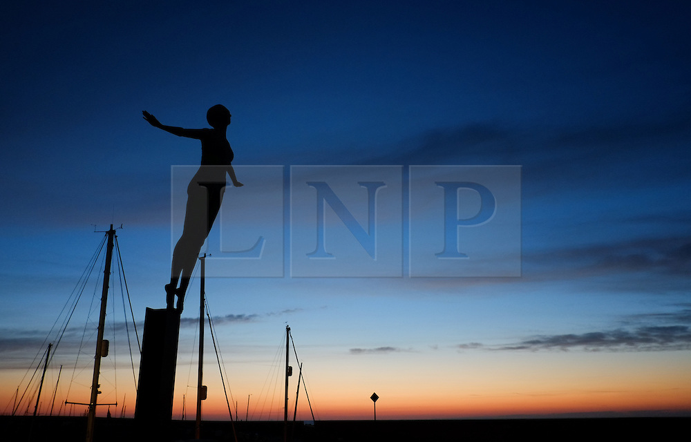 © Licensed to London News Pictures. <br /> 05/10/2014. <br /> <br /> Scarborough, United Kingdom<br /> <br /> A statue on a sea wall stands tall over the fishing boats and yachts that are moored up in the harbour at Scarborough, North Yorkshire as dawn breaks over the north sea.<br /> <br /> Photo credit : Ian Forsyth/LNP