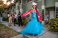 On Friday, May 8, 2020 Trenisha Maxwell, 17, of Miami Norland Senior High School wears her senior prom dress and the graduation cap and sash she would have worn for graduation with her fellow classmates but all canceled due to COVID-19. Her sisters Taquisha Maxwell, holding Summer McCarthy 1, and Telesha Maxwell, holding Autumn McCarthy, 10 months , while mom Michelle Maxwell, 41 takes pictures. At right is friend Trinity wood, 17, who is social distancing.