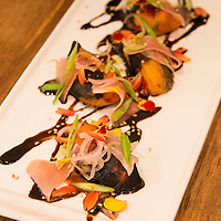 A plate of grilled South Carolina peaches with Benton's Country Ham, Pickled Shallots, Benne Seeds, Local Tamari, Scallions, Shiso. Chef John Fleer's restaurant Rhubarb is located at 7 SW Pack Square in Downtown Asheville, North Carolina.