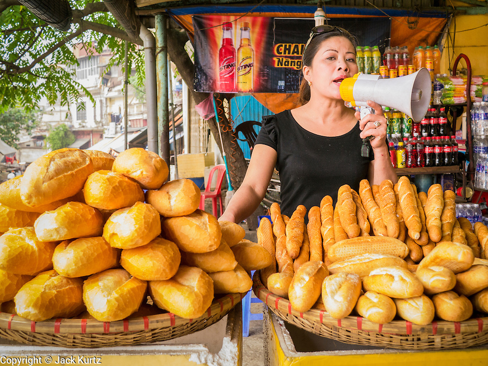 06 APRIL 2012 - HANOI, VIETNAM: A woman sells crusty French bread in the Long Bien Train station in Hanoi. The Hanoi to Hai Phong Express Train runs several times a day between Long Bien Station in Hanoi and the Hai Phong Station. Hanoi is the capital of Vietnam and Hai Phong is the 4th largest city in Vietnam. Hai Phong is the principal industrial port in the northern part of Vietnam. It was heavily bombed and mined during the American War (what Americans call the Vietnam War).   PHOTO BY JACK KURTZ