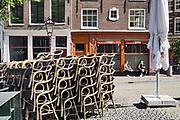 Nederland, Amsterdam, 7-5-2020 Per 1 juni mogen de cafes en andere horeca weer open en bedienen op terrassen voor 30 mensen en met anderhalve meter tussenruimte . De horeca is al enkele weken gesloten vanwege de coronadreiging maar de regering laat het normale dagelijks leven weer langzaam opstarten . Opgestapelde stoelen in de binnenstad van Amsterdam . Unlock,beperkende,beperkingen, opheffen,versoepelen,versoepeling , opengooien. Foto: Flip Franssen