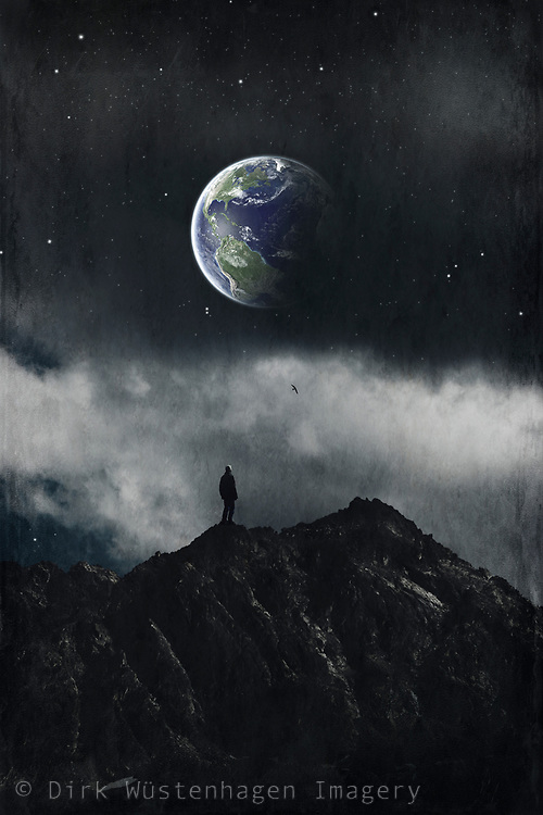 Man on a mountain range looking at Earth