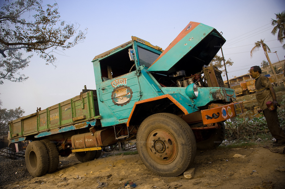 Truck mechanic and old truck on the Grant Trunk road outside of Kolkata.