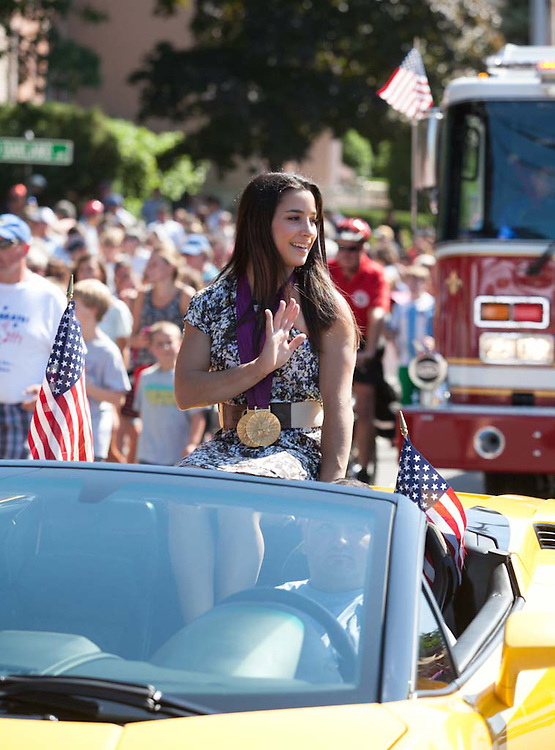 Needham, MA 08/26/2012.Gymnast Aly Raisman waves from a yellow Lamborghini as she travels down Highland Ave during Sunday's parade..Wicked Local Photo by Alex Jones