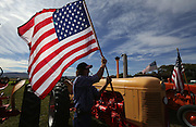 A man attaches the Stars and Stripes to a 1955 Case tractor at the annual threshing bee and old-farm-equipment gathering in Ellensburg's Olmstead Place State Park. (Alan Berner/The Seattle Times)