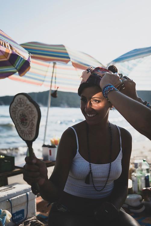 Ivanna Kollmann, from Argentina, looks in a mirror at Salinas Beach. (August 4, 2018)