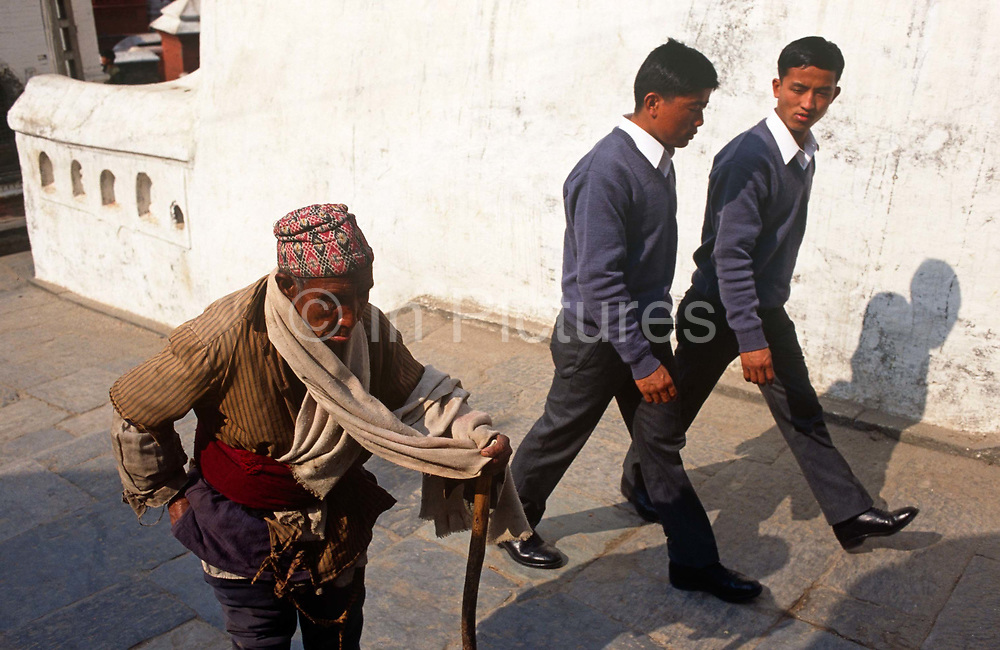 Young Nepali boys stride past poor elderly man in Kathmandu street after recruitment into the British Gurkhas. Trying for places in the Gurkha Regiment is part of a tough endurance series to find physically perfect specimens for British army infantry training. They will need to perform 25 straight-kneed sit-ups at a 45° slant both within 60 seconds to pass. 60,000 boys aged between 17-22 (or 25 for those educated enough to become clerks or communications specialists) report to designated recruiting stations in the hills each November, most living from altitudes ranging from 4,000-12,000 feet. After initial selection, 7,000 are accepted for further tests from which 700 are sent down here to Pokhara. Only 160 of the best boys succeed in the journey to the UK. The Gurkhas have been supplying youth for the British army since the Indian Mutiny of 1857.