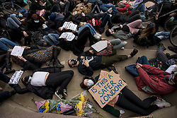 © Licensed to London News Pictures. 14/03/2021. London, UK. Protestors lie down and perform a die in outside Parliament in London for a demonstration, organised by Sisters Uncut, against the actions of the police force at a vigil for murdered Sarah Everard yesterday evening. There have been calls for Met Chief Cressida Dick to resign following yesterday's scenes, when police dragged women away from a bandstand as thousands gathered in Clapham, South London. Photo credit: Ben Cawthra/LNP