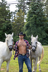 hot cowboy with open shirt holding two white horses on a ranch
